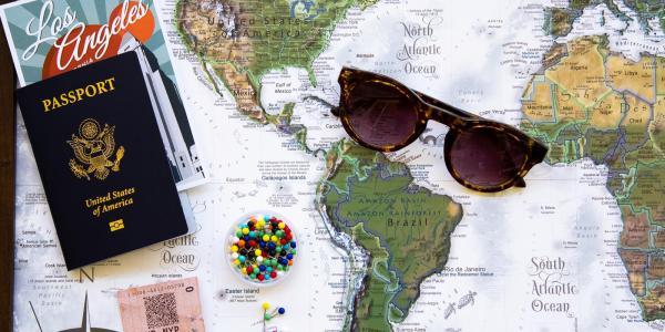 laydown of map, passport, sunglasses, travel brochure