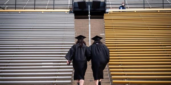 Graduates walking up steps at Folsom Field