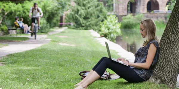 Grad student works on laptop while leaning against a tree