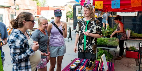 Charlie visits with customers at Boulder Farmer's Market