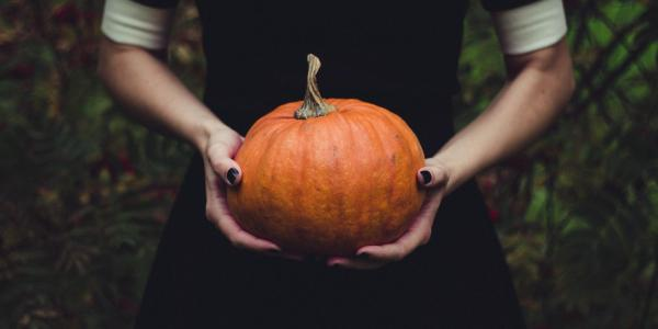 Woman in black dress holds a small orange pumpkin in her hands