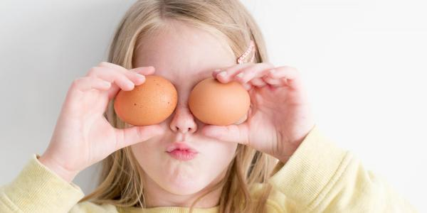 A girl holds brown eggs over her eyes. (Photo by Hannah Tasker on Unsplash)