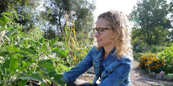 Professor Jill Litt looks over an eggplant at a community garden next to Regis University in Denver