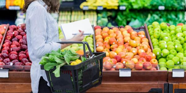 Person grocery shopping for produce with paper list in hand