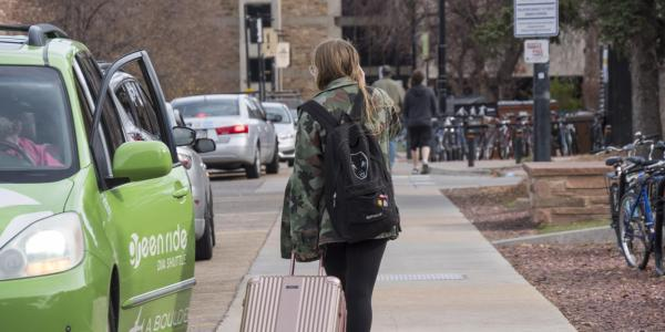 Student leaving campus with suitcase