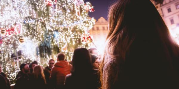 People gather around a Christmas tree at an outdoor festival