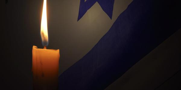 Candle burns with Jewish star in background