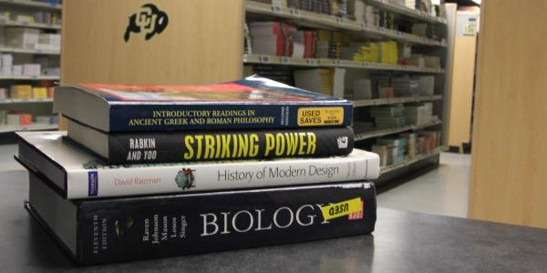 stack of textbooks at the CU Book Store