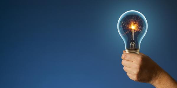 Hand holds out lightbulb