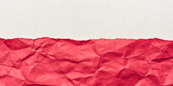 Red wrinkled paper against a white background