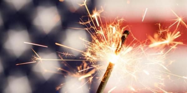 Sparkler in front of American Flag.