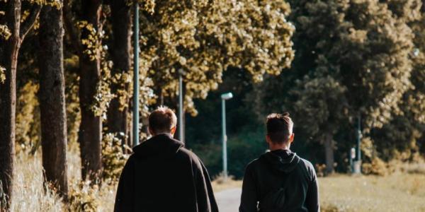Two people walking in an autumn scene.