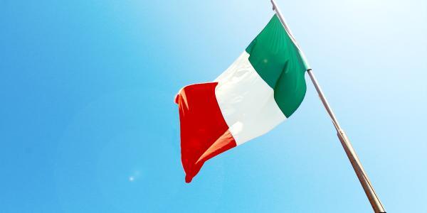 Italian flag flies in clear blue sky