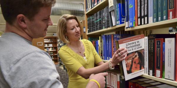 Jennifer Knievel and a student look at a book from the library shelf.