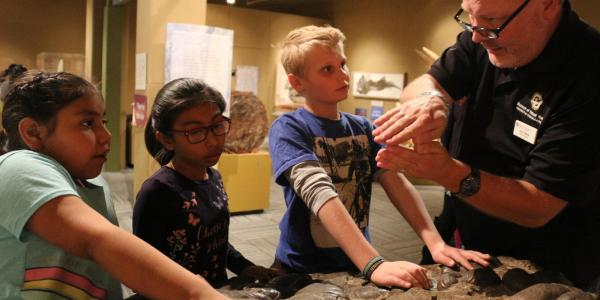 Museum educator Jim Hakala describes a clam shell fossil to University Hill Elementary School students in Boulder