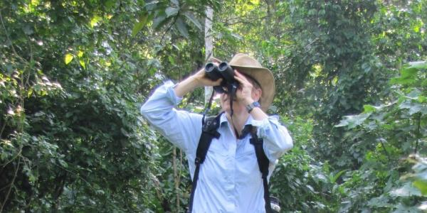 Joanna Lambert standing on tree limb and looking through binoculars.