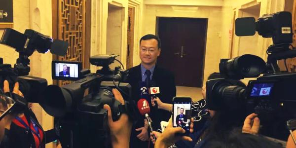 Professor John Zhai speaking with news media at the World IoT Exposition in China