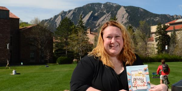"Karstee Davis holding ""Eat Pray Love"" book in front of the Flatirons"