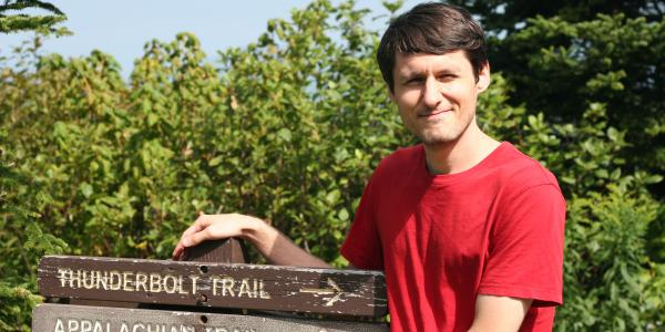 Keane Southward in front of trail signs