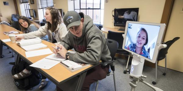 Student Annie Miller joins class remotely via Kubi robotic device