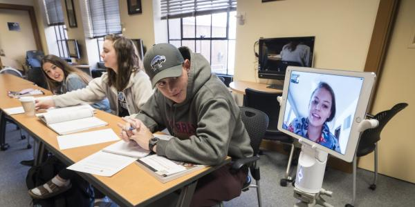 "Anne Miller, a CU Boulder International Affairs major, uses new OIT technology called ""Kubi"" (Japanese word for neck) to attend an Arabic language class face-to-face while recovering from an injury."