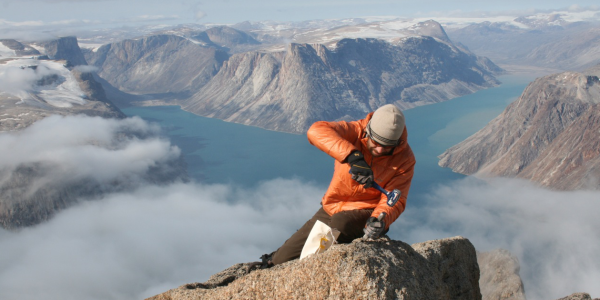 Researcher taking a sample atop a mountain