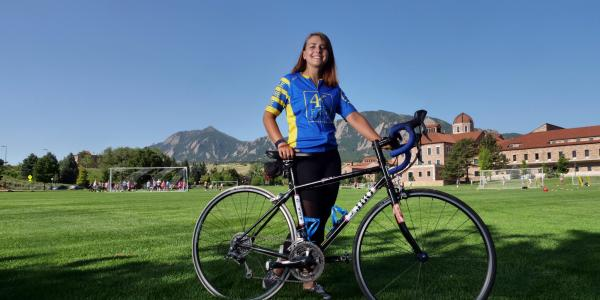 Lauren Gray and bike with Flatirons in the background