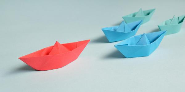 red paper boat leads a pack of blue and green paper boats