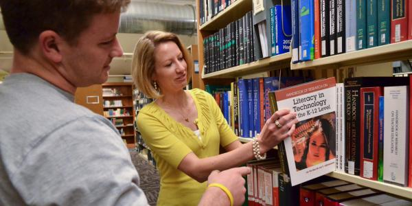 Library staff member pulls a textbook from the shelf