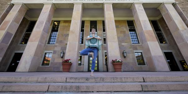 Lori Hunter demonstrates yoga pose in the steps of Norlin Library