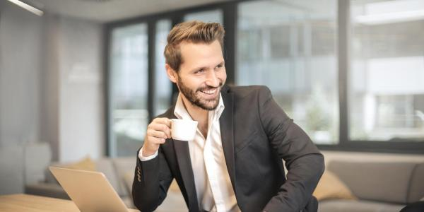 A man laughing while holding a teacup (Photo by Pexels)
