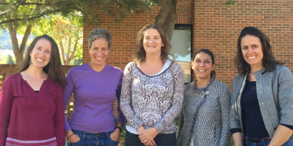 The team of grant recipients, five women from Mental Health Partners and CU Boulder, stand in a row and pose for a photo, smiling.