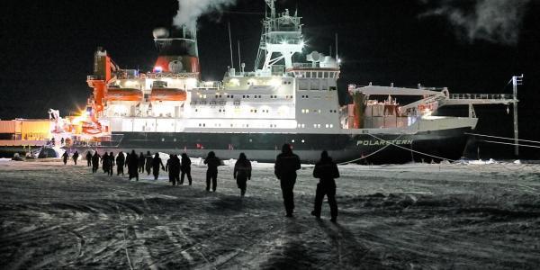 People walk across the ice  toward Polarstern. Photo by Michael Gutsche.