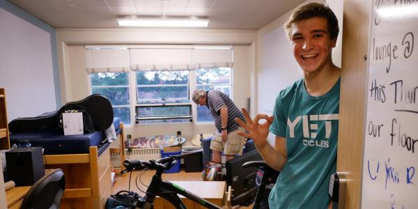 Student moving into dorm room with bicycle in background