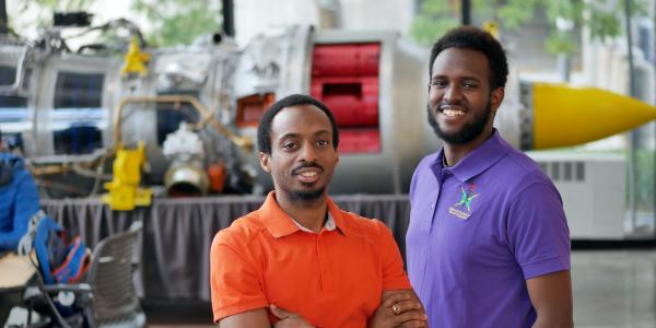 Yohannese Gebremedhin, right, and Arthur Antoine, left, stand in front of a model of a rocket in the engineering center on the University of Colorado Boulder campus.