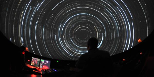 Instructor watches star trails while teaching a class in Fiske Planetarium