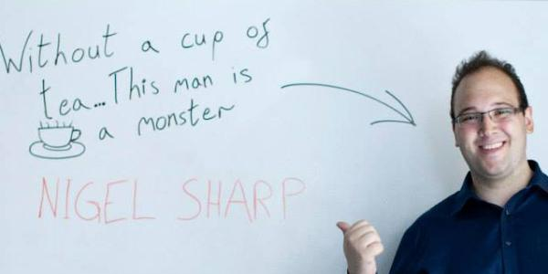"""Nigel Sharp next to a whiteboard that reads """"Without a cup of tea... This man is a monster"""""""