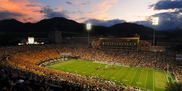 Fans cheer as the sun sets at Folsom Field