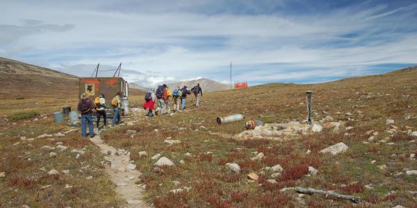 Journalists walk along dirt path in Niwot, Colorado