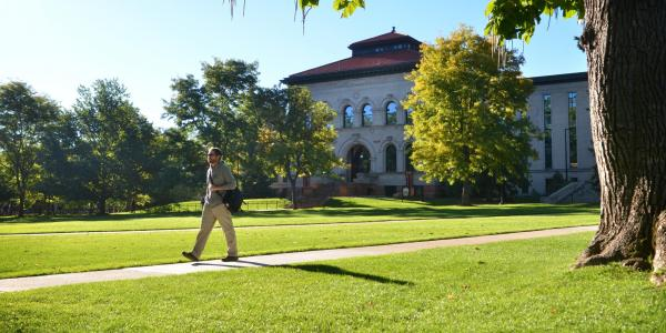 Campus community member walks across Norlin Quad