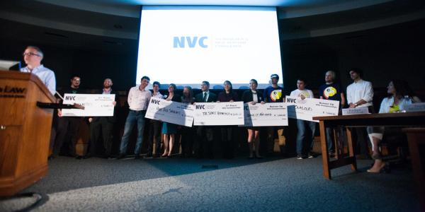 New Venture Challenge finalists pose with giant checks on stage