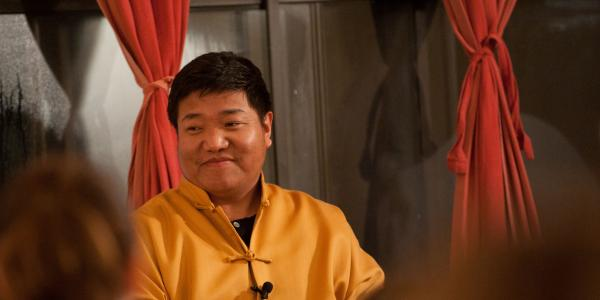 Orgyen Chowang Rinpoche sits in front of curtains