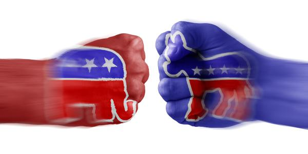 Two human fists, one painted blue with the Democratic donkey and the other red with the Republican elephant. face off knuckle-to-knuckle.