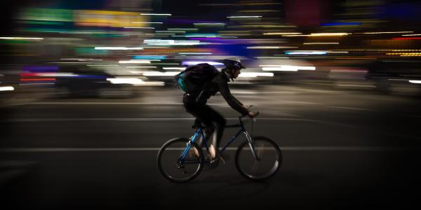 person riding bike at night with no lights