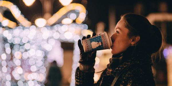 Woman sipping hot drink, looking at holiday lights