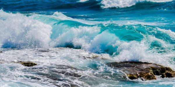 Photo of waves crashing in the ocean.