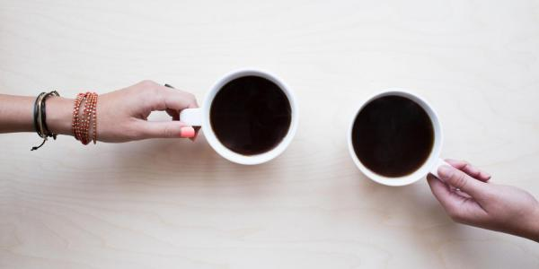 two people having a conversation over coffee