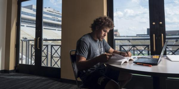 CU Buffaloes football running back Phillip Lindsay studies in the Dal Ward Center located next to Folsom Field. (Photo by Glenn Asakawa/University of Colorado)