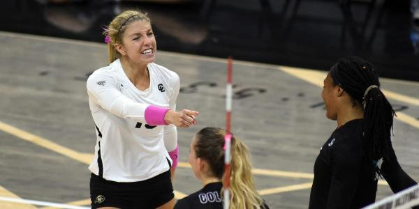 A CU volleyball player wears pink during a match