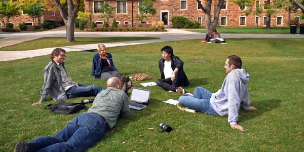 students sit in a circle outside on campus